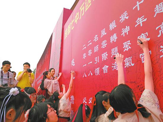 成都七中万达学校即将参加高考的学生在高考签名墙签名。