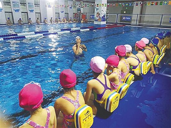 海口市港湾小学学生在校内游泳池学游泳。学校供图