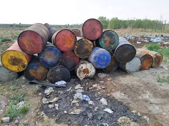 部分油桶已泄漏,严重污染了周边土地。