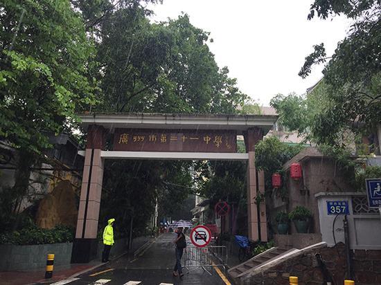 广州市第二十一中校门外,安保人员在暴雨中执勤。