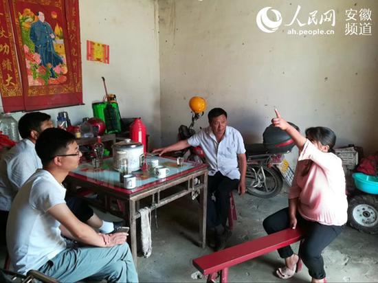 资料图:华同春(右二)走访贫困户