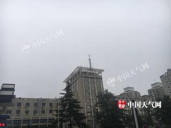 今晨6时左右北京国家图书馆附近天空阴沉,还有雨点飘落。