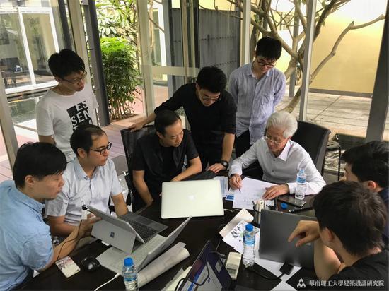 何镜堂和团队工作人员一起讨论方案。
