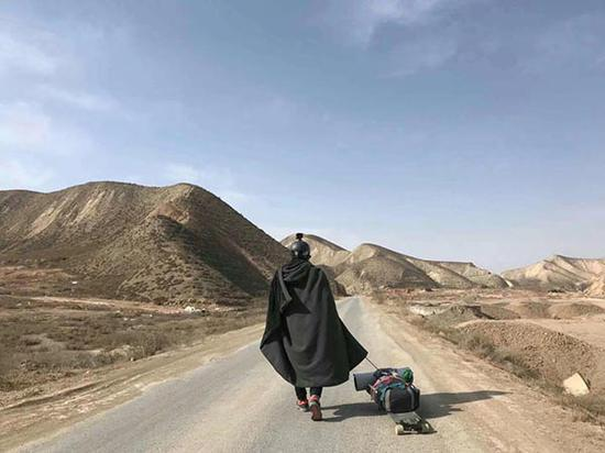 """""""骆驼兄弟""""穿着黑色的披风,拉着行李走在旅途上。受访者供图"""