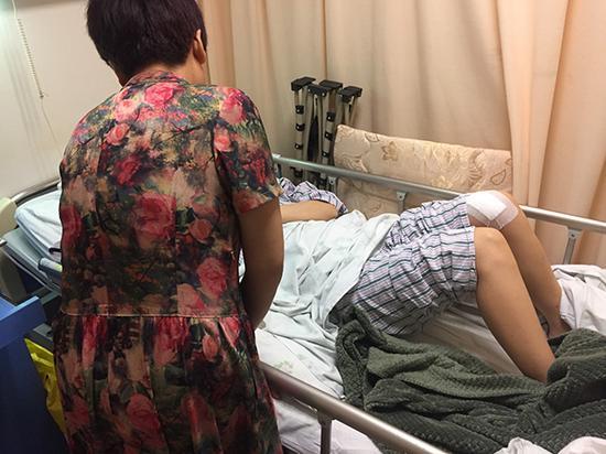 黄小妮躺在医院病床上,母亲在身旁照顾。澎湃新闻见习记者 李佳蔚 图