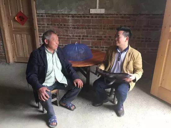 蓝标河(右)在融安县大坡乡同仕村与贫困群众座谈交流。图片来源于网络