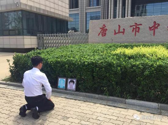 ▲获无罪后,廖海军在法院门前朝父母遗像磕头告慰。新京报记者 赵凯迪 摄
