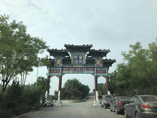 """孟门镇李家塔村被称为""""陈家大院""""的新小区外写着""""富而思源""""四个字。"""