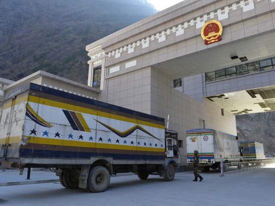 2015年12月30日,尼泊尔大货车在西藏日喀则吉隆口岸排队接受出关检查。(新华社记者刘东君摄)