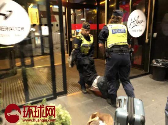 中国游客曾先生的父亲被瑞典警察抬出旅店。