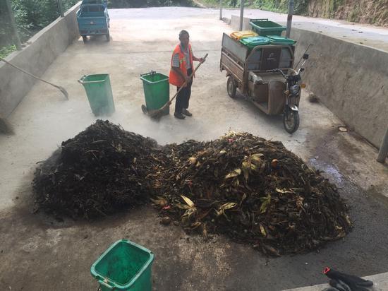 """李传喜(化名)正在龙溪村的堆肥场给厨余垃圾""""翻堆""""。新京报记者张胜坡摄"""