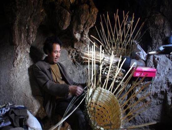 老人平时在洞里编制竹器售卖。