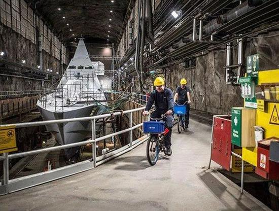 ▲图为穆斯克水师基天公开船厂内,两名瑞典水师兵士骑自止车从一艘维斯比级隐身保护舰旁驶过。(瑞典国防部网站)