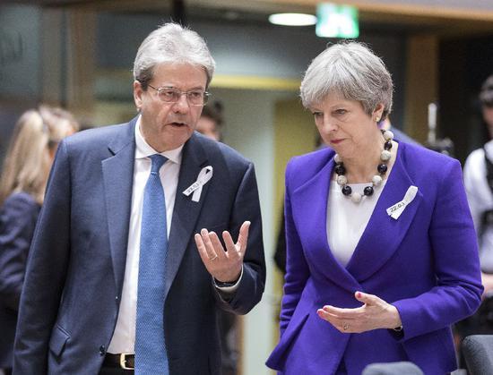 ▲欧盟春季峰会上,意大利总理真蒂洛尼(左)和英国首相特雷莎・梅交流。 图/新华社