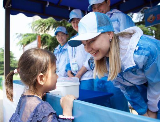 6月8日,在位于青岛香港中路的一处志愿服务驿站,青岛大学国际教育学院的俄罗斯留学生奥列加(前右一)在用汉语与一名小女孩交流。6月9日至10日,上海合作组织成员国元首理事会第十八次会议将在青岛举行。几名来自青岛大学的留学生志愿者在位于青岛香港中路的志愿服务驿站,为过往路人提供语言翻译、交通引导、信息咨询等服务。新华社记者姜克红摄