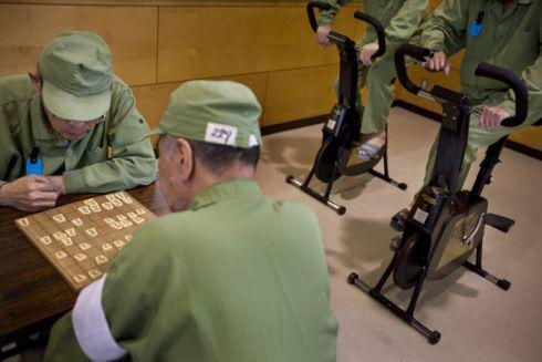 娱乐室里,玩日本将棋的老年囚犯,一旁还有两名囚犯使用动感单车。