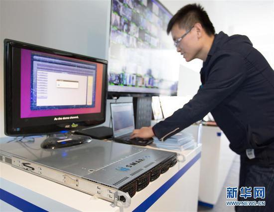 2017年12月,北京智能计算产业研究院举行的发布会上,工作人员现场演示高通量人工智能一体机的应用。(图片来源:新华社)