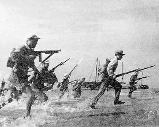 ▲资料图片:解放海南岛战役历史照片,可见正在冲上滩头的解放军战士。