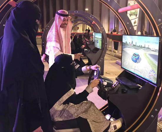 6月23日晚,一名沙特女性在利雅得关于女性驾车交通安全宣传活动上模拟驾车。新华社记者王波摄