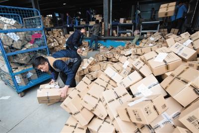13日,北京一家快递公司的工作人员正在分拣快件。新京报记者 王子诚 摄