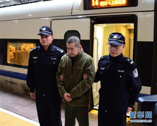 """11月18日,在汉口火车站,犯罪嫌疑人王某在警方押送下抵达武汉。当日,一名涉嫌骗取贷款,被国际刑警组织发布红色通缉令的重大经济犯罪案件外逃嫌疑人从加拿大回武汉自首。据武汉警方介绍,嫌疑人王某是""""猎狐行动""""开展以来,武汉首个自愿从西方国家回国自首的境外逃犯。此前,追逃专班曾先后10次派人登门探望慰问王某父母,解决其生活困难。"""