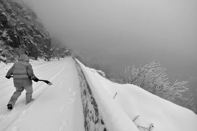 ▲今天,门头沟公路分局京门维护段工人在妙峰山路上除雪。京华时报记者王海欣摄