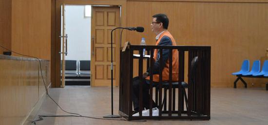 2014年12月11日,江西省南昌市,上午10时,庭审开始,原南昌大学校长周文斌出庭并坐在被告席上,答辩护人讯问时,周文斌面无表情,神情冷漠。摄影师:王樊