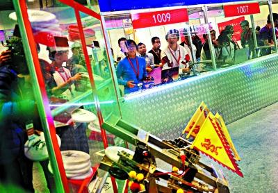 """比赛中,潘逸凡和周慧轩在操作台指挥机器人来到""""填弹""""窗口,补充飞盘。机器人一次只能填充三枚飞盘,可以多次填充,多次发射。"""