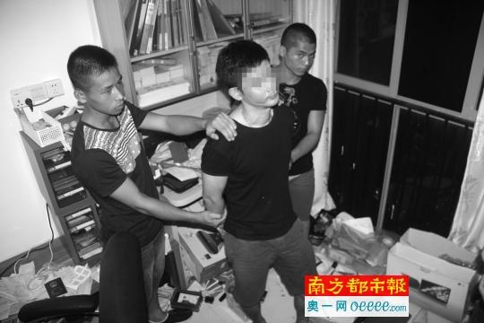 2014年7月9日,江门支队侦查员押解本案一号主犯李某白(中)到深圳家中搜查取证。
