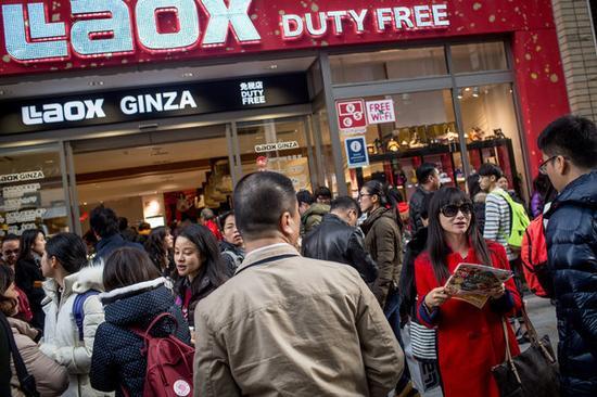 日本是春节期间中国游客最喜爱的目的地之一。2月20日,一群游客下了旅游大巴,等待进入一家免税商店。