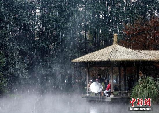 12月5日,浙江杭州,杭州降下2015年入冬第一场雪。西湖的水面上飘起层层白雾。林云龙 摄