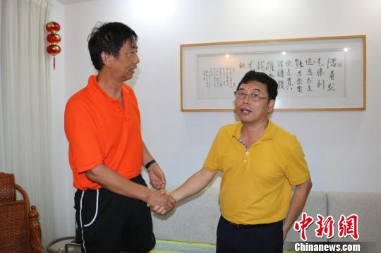12月8日,毕国昌白叟的家中,三亚市咫尺区副区长张守让(右)与毕国昌握手。 尹海明 摄