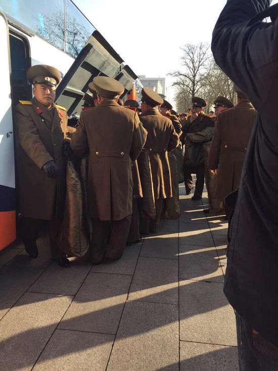 功勋国家合唱团成员依次从大巴车中取出行李