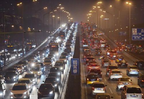 2015年12月7日,汽车在雾霾笼罩下的北京东三环国贸桥上行驶。新华社记者 罗晓光摄