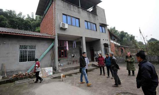 18日,四川隆昌县红土村一组张家门前,街坊及亲人们谈论着。下游新闻记者 李斌 摄