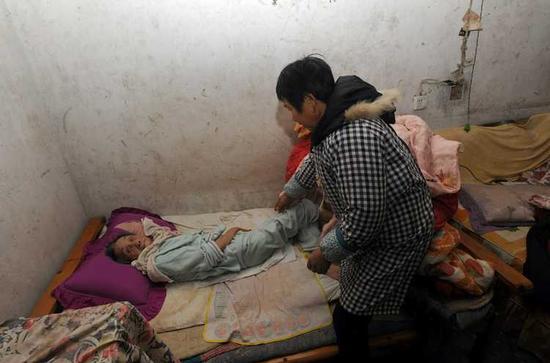 18日,四川隆昌县红土村一组张家,他大姐张成蓉正给瘫痪的母亲翻身材。下游新闻记者 李斌 摄