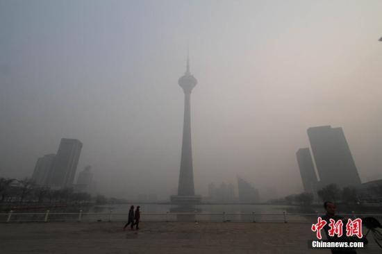 """12月14日下午,天津市地标修筑之一的""""天塔""""在雾霾掩映中。 中新社记者 张道正 摄"""