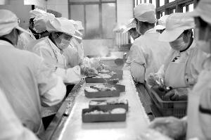 食堂作业人员将饭菜分装到餐盒里 当代快报记者 徐洋 摄