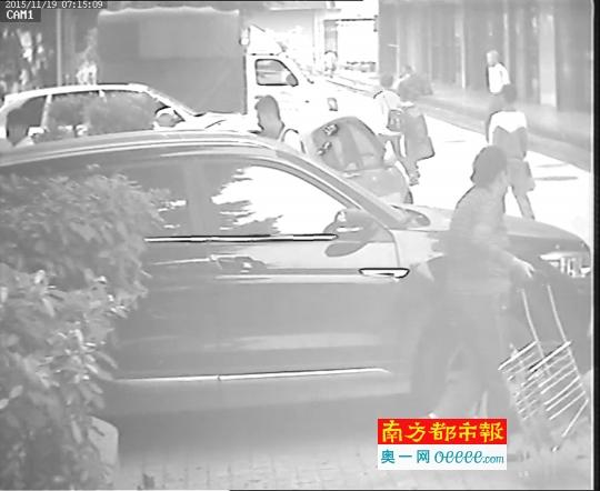 监控视频拍到刮车人右手拖着买菜的篮子车,左手往车上蹭。 视频截图