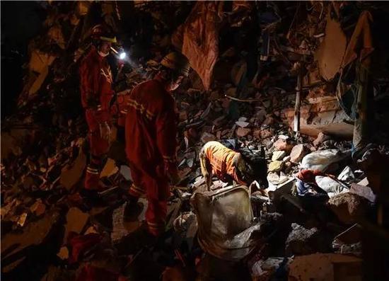 12月20日,消防官兵在利用搜救犬搜救。新华社记者 毛思倩摄