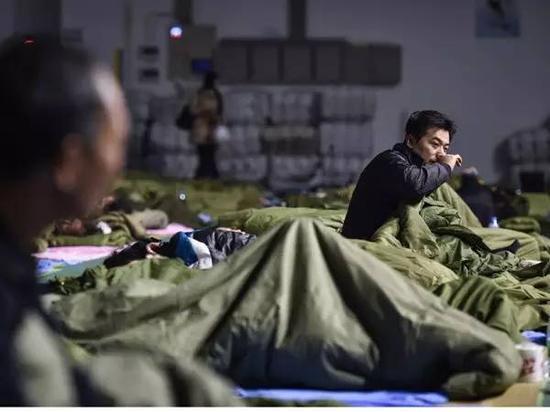 12月21日,撤离的群众在深圳市光明新区群众体育中心休息。新华社记者毛思倩摄