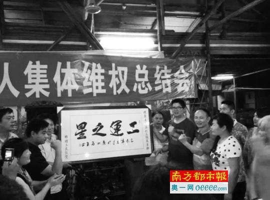 """利得鞋厂工人在庆功宴上向曾飞洋赠送""""工运之星""""牌匾。警方称,该牌匾是曾飞洋自己掏钱请工人制作的。图片来源:南方都市报"""