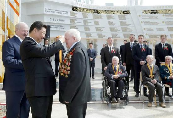 5月11日,国家主席习近平同白俄罗斯总统卢卡申科在明斯克卫国战争历史博物馆会见15名白俄罗斯第二次世界大战老战士代表。这是习近平向老战士颁发纪念奖章。 新华社记者 鞠鹏 摄