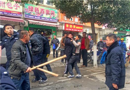 """持棍男子喊着:""""连孕妇都打,刚刚是谁动的手?""""有人指向一辆城管执法车内驾驶座的城管队员,持棍男子冲上前,再次发生冲突,城管队员脸部有血迹。"""