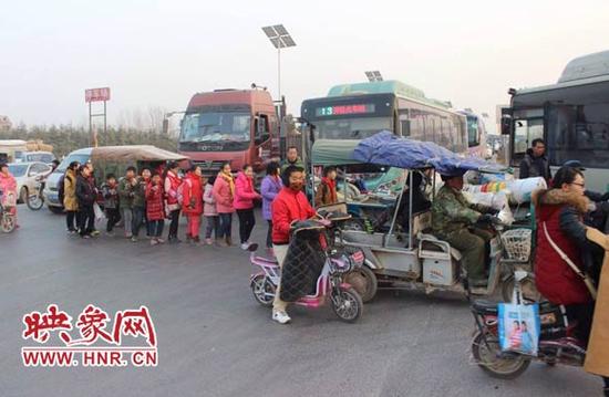 在郑州市郑新快速路南曹乡苏庄村附近,因十字路口无红绿灯,学生们放学必须排队过马路,从大货车面前穿行。
