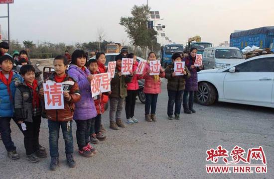 """几名学生举着""""请领导陪我们过马路""""的牌子,引起了过路人的围观。"""