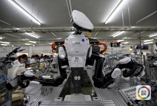 图为日本一家工场中,一台产业机械人与工人一同在流水线上事情(图像来历:新华/路透)