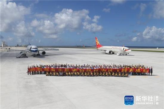 1月6日,两架民航客机下降南沙永暑礁新建机场。这是关联职员合影纪念。新华社记者邢广利摄
