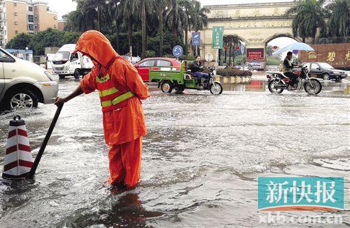 大雨之后,广州碧桂园前水浸严重,市政工人在疏通下水道。