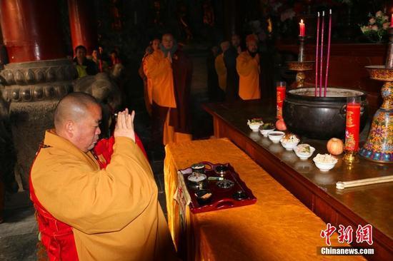 图为上午8时30分,少林寺大雄宝殿,方丈释永信大和尚带领僧众做了一场小规模的供奉法会,为信众祈福。